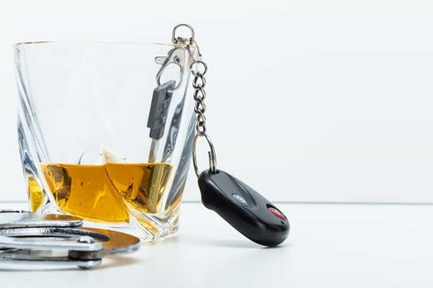 Keys in a Cup of Alcohol Next to Cuffs